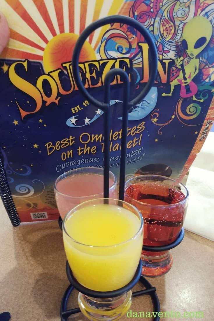 Squeeze In menu behind three drinks