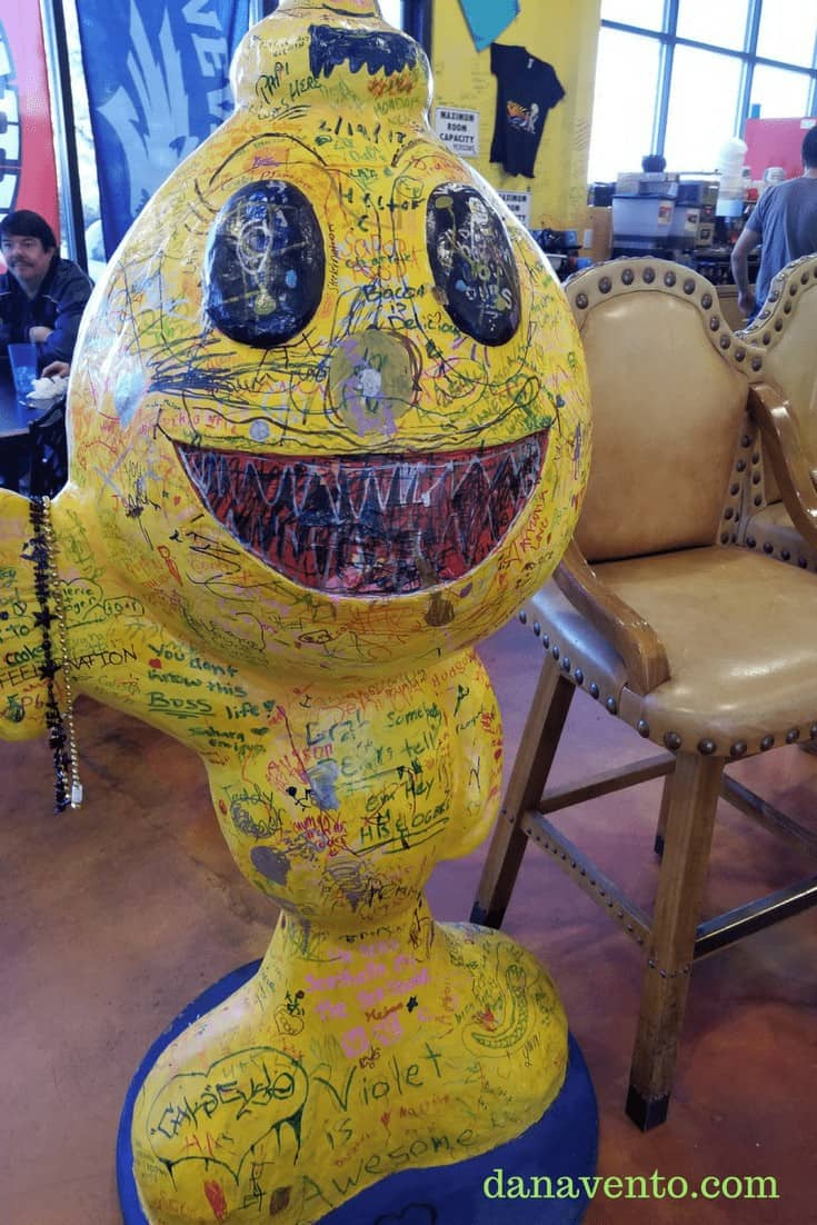 Smiley face statue decorated with drawings
