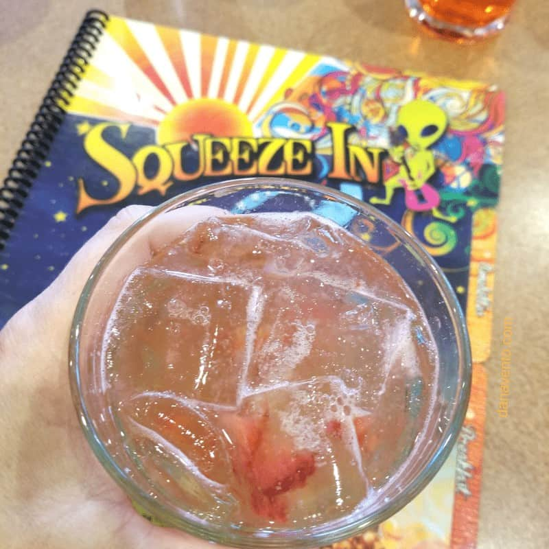 Hand holding a cocktail over Squeeze In menu