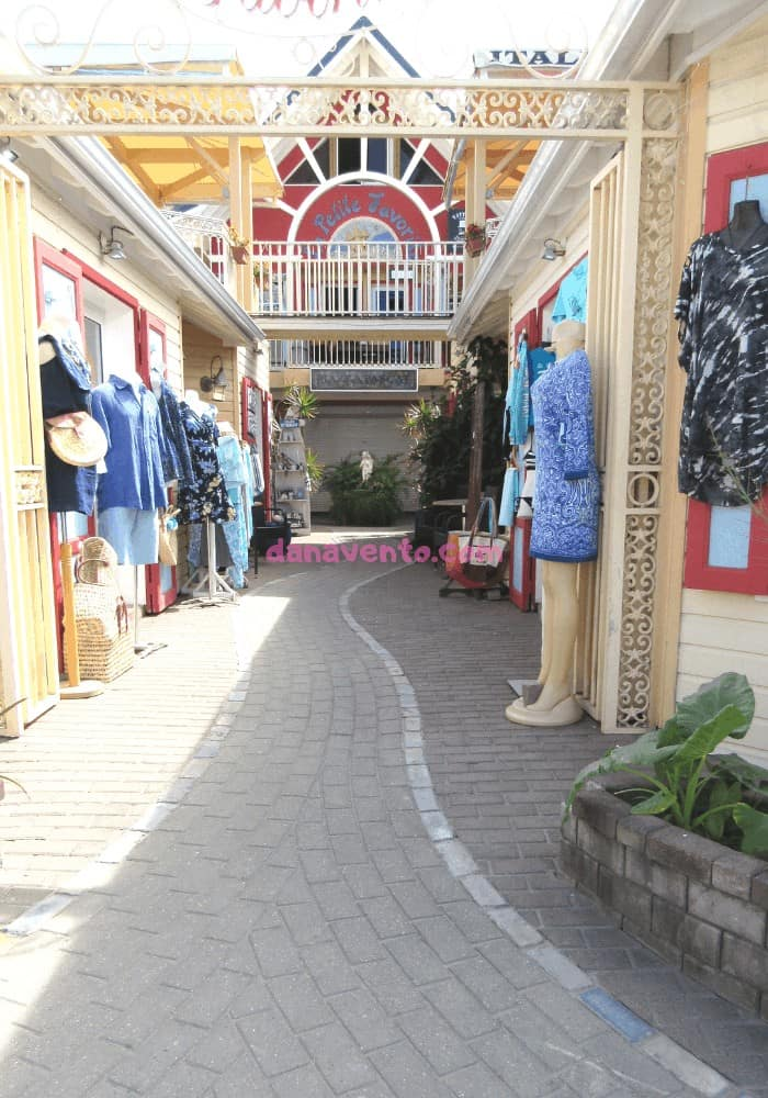 Street lined wtih mannequins displaying clothing.