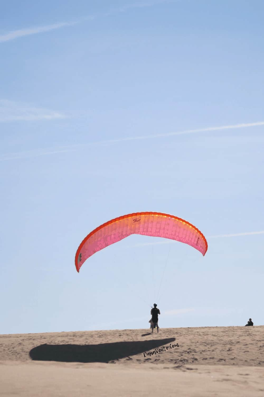 standing with hang glider in the outer banks and sunglasses on